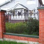 Металлический забор с пиками на кирпичных столбах