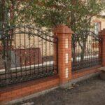 Волнистый кованый забор на кирпичных столбах