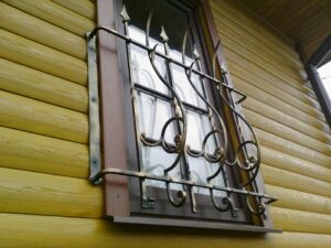 Защитная кованая оконная решетка на деревянном срубе