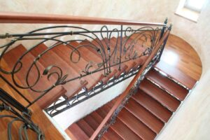 Кованая лестница с деревянными ступенями в частном доме