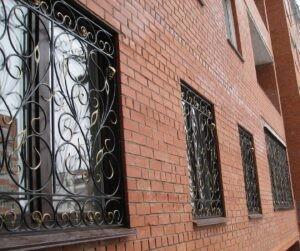 Кованые решетки на окнах кирпичной стены