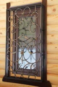 Небольшая кованая решетка на деревянной стене