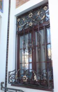 Кованая оконная решетка с цветочницой