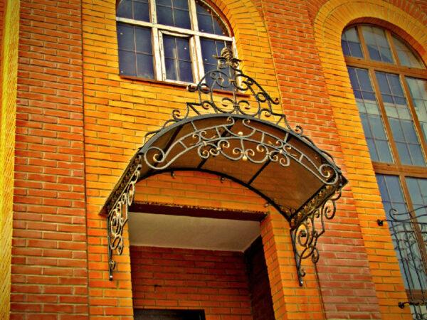 Кованый арочный козырек на стене из кирпича Артикул № 040