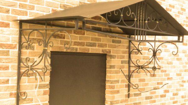 Двухскатный кованый козырек над входом в дом